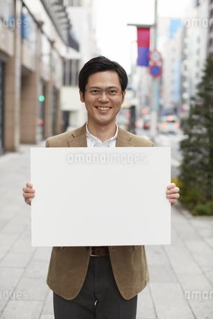 街でホワイトボードを持つ男性の写真素材 [FYI02967225]