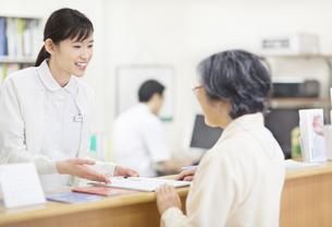 笑顔で受付をする女性看護師の写真素材 [FYI02967226]