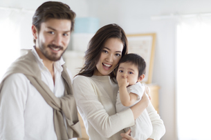 微笑む男性と赤ちゃんを抱き抱える女性の写真素材 [FYI02967233]