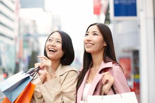 買い物中に上を見て微笑む女性二人の写真素材 [FYI02967234]