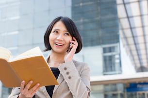 ビルの前で電話するビジネス女性の写真素材 [FYI02967237]