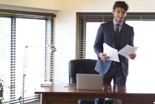 オフィスで資料を持ち微笑むビジネス男性の写真素材 [FYI02967240]
