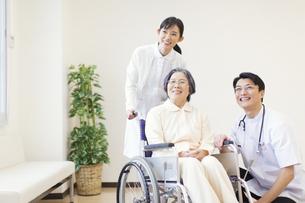 車椅子の患者に添う男性医師と女性看護師の写真素材 [FYI02967241]
