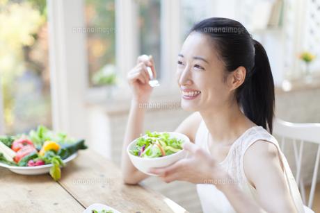 サラダを食べる笑顔の女性の写真素材 [FYI02967242]
