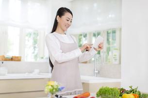 キッチンでタブレットPCを見る奥さんの写真素材 [FYI02967244]