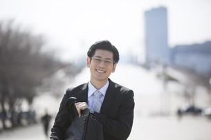 カバンを手に笑うビジネス男性の写真素材 [FYI02967245]