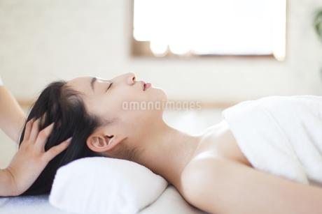 仰向けで頭をマッサージされている女性の写真素材 [FYI02967246]