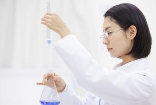 フラスコと試験管を使って研究をしている女性研究員の横顔の写真素材 [FYI02967249]