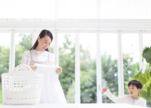 洗濯物を見る奥さんと男の子の写真素材 [FYI02967254]