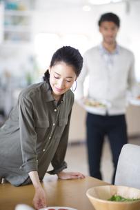 ダイニングテーブルで料理の準備をする男性と女性の写真素材 [FYI02967257]