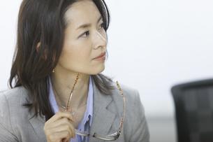眼鏡を持って話を聞くビジネス女性の写真素材 [FYI02967266]