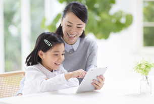 母の持つタブレットPCにタップする女の子の写真素材 [FYI02967278]