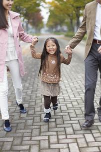 両親と手をつないで喜ぶ女の子の写真素材 [FYI02967280]