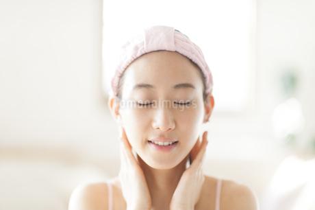 首に両手を添えて目を瞑る女性の写真素材 [FYI02967282]