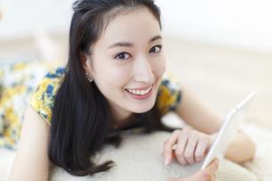 タブレットPCを手に笑顔の女性の写真素材 [FYI02967283]