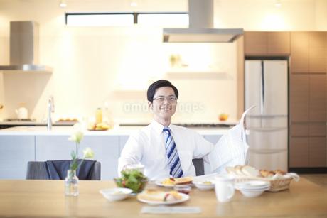 出勤前の朝食中に顔をあげて微笑む男性のスナップの写真素材 [FYI02967286]