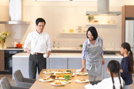 テーブルに食事を用意する家族の写真素材 [FYI02967288]
