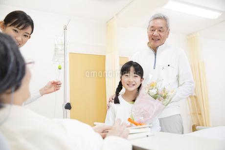 お見舞いにきて花束を渡す女の子の写真素材 [FYI02967291]