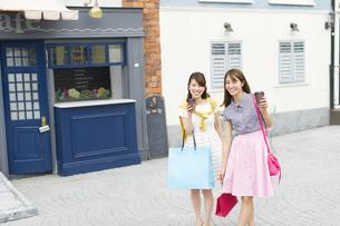 カップを持ってショッピングを楽しむ2人の女性の写真素材 [FYI02967299]