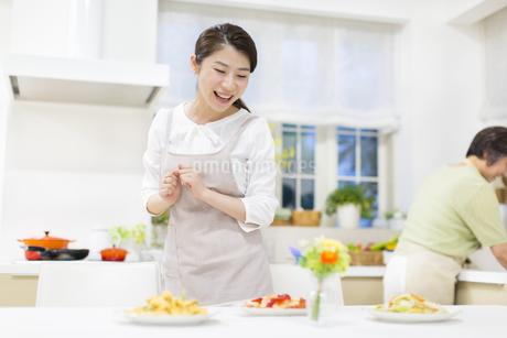 食卓の料理を見て喜ぶ若い奥さんの写真素材 [FYI02967305]
