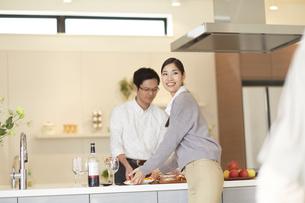 キッチンから食事を運ぼうとする女性の写真素材 [FYI02967308]