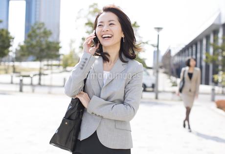 立ち止まって電話をするビジネス女性の写真素材 [FYI02967312]