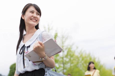 新緑を背景に歩く女子学生の写真素材 [FYI02967316]