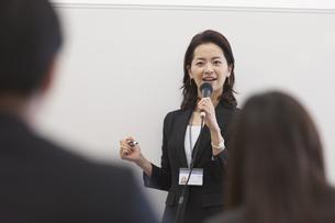 マイクを手に講義するビジネス女性の写真素材 [FYI02967319]