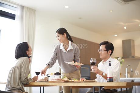 ホームパーティで談笑する男女三人の写真素材 [FYI02967320]