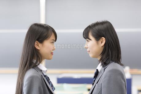 教室で見つめ合う2人の女子高校生の横顔の写真素材 [FYI02967327]