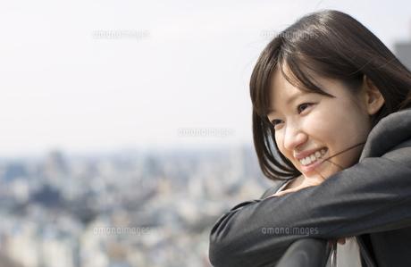 柵に肘をかけて微笑むビジネス女性の写真素材 [FYI02967328]