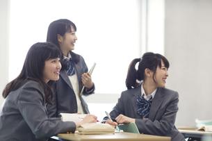 教室で同じ方向を眺める3人の女子高校生の写真素材 [FYI02967331]