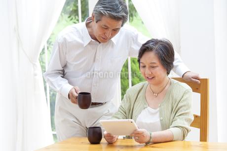 テーブルでタブレットPCを見るシニア夫婦の写真素材 [FYI02967332]