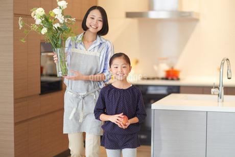 花とリンゴを持ってダイニングを歩く親子の写真素材 [FYI02967333]