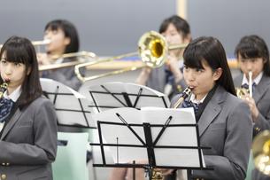 音楽室で吹奏楽の練習をする女子学生たちの写真素材 [FYI02967334]