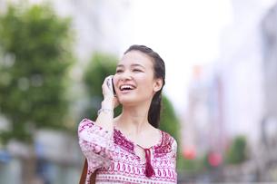 街中でスマートフォンで話す若い女性の写真素材 [FYI02967335]