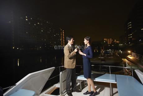 夜景をバックにクルーザーの上で乾杯するカップルの写真素材 [FYI02967337]