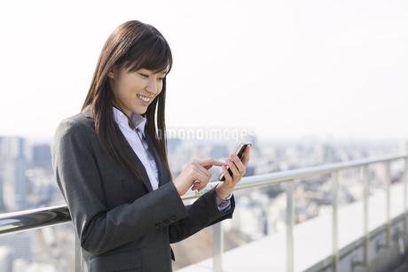 屋上でスマートフォンにタッチするビジネス女性の写真素材 [FYI02967339]