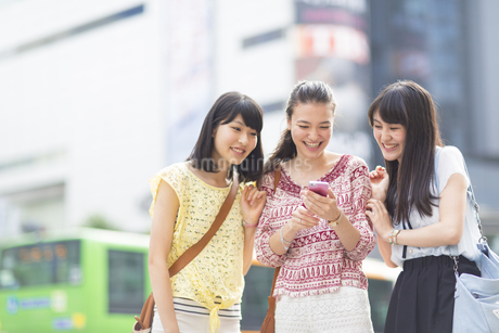 スマートフォンを見つめて喜ぶ3人の若い女性の写真素材 [FYI02967341]