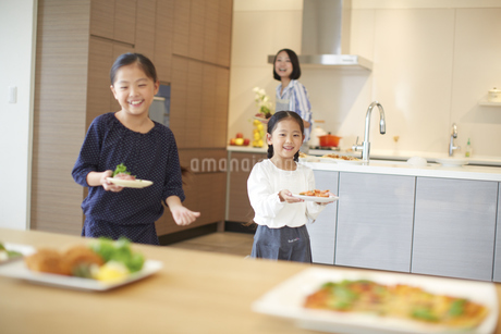 テーブルに食事を用意する親子の写真素材 [FYI02967346]