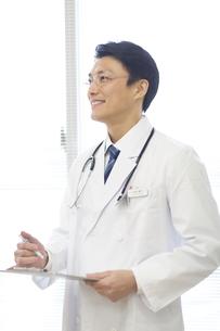 窓際でカルテを持って見上げる男性医師の写真素材 [FYI02967348]