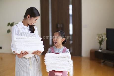 たたんだタオルを持って笑い合う親子の写真素材 [FYI02967351]
