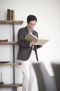 棚にもたれて本を読む男性の写真素材 [FYI02967355]