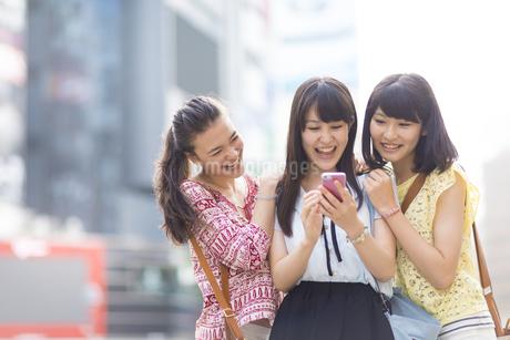 スマートフォンを見つめて喜ぶ3人の若い女性の写真素材 [FYI02967357]