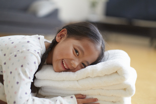 置いたバスタオルに顔をのせて笑う女の子の写真素材 [FYI02967360]
