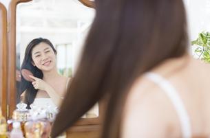 鏡台で髪をとかす女性の写真素材 [FYI02967363]