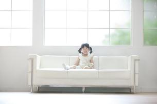 ソファーに座って笑う女の子の写真素材 [FYI02967364]