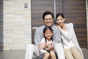 家の前でほほ笑む3人家族の写真素材 [FYI02967367]