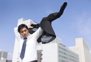 ビルを背景にジャケットに袖を通すビジネス男性の写真素材 [FYI02967371]