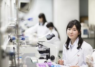 顕微鏡の前で微笑む女子学生の写真素材 [FYI02967374]